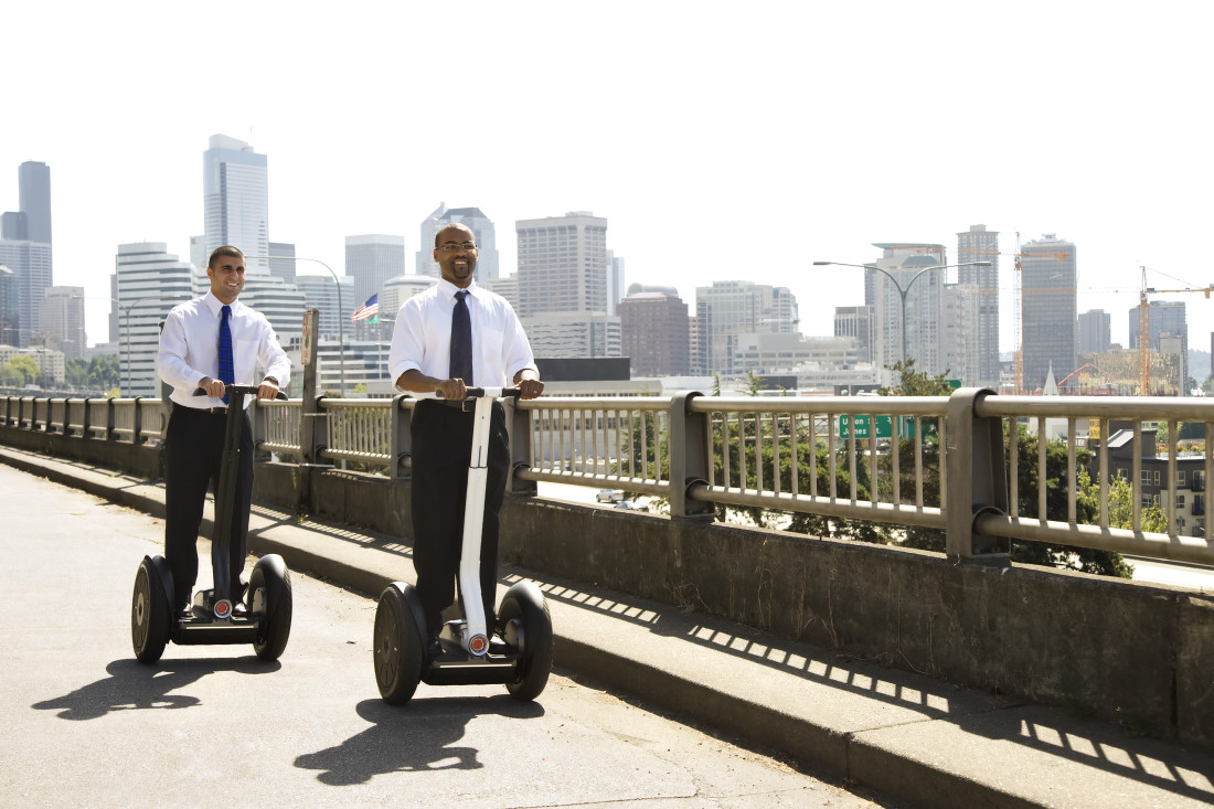 Two business men travelling on segways