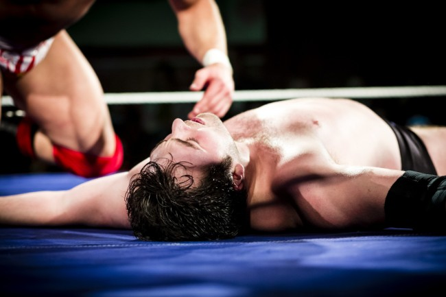 Pro wrestler, lying on the floor being counted out