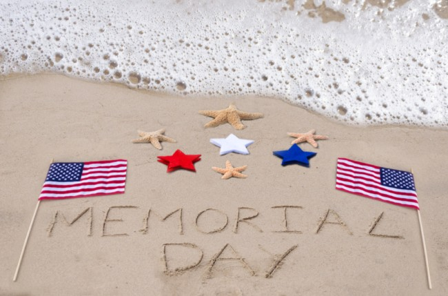 """Memorial Day carved out on beach sand with flags and blue, white, and red stars"""